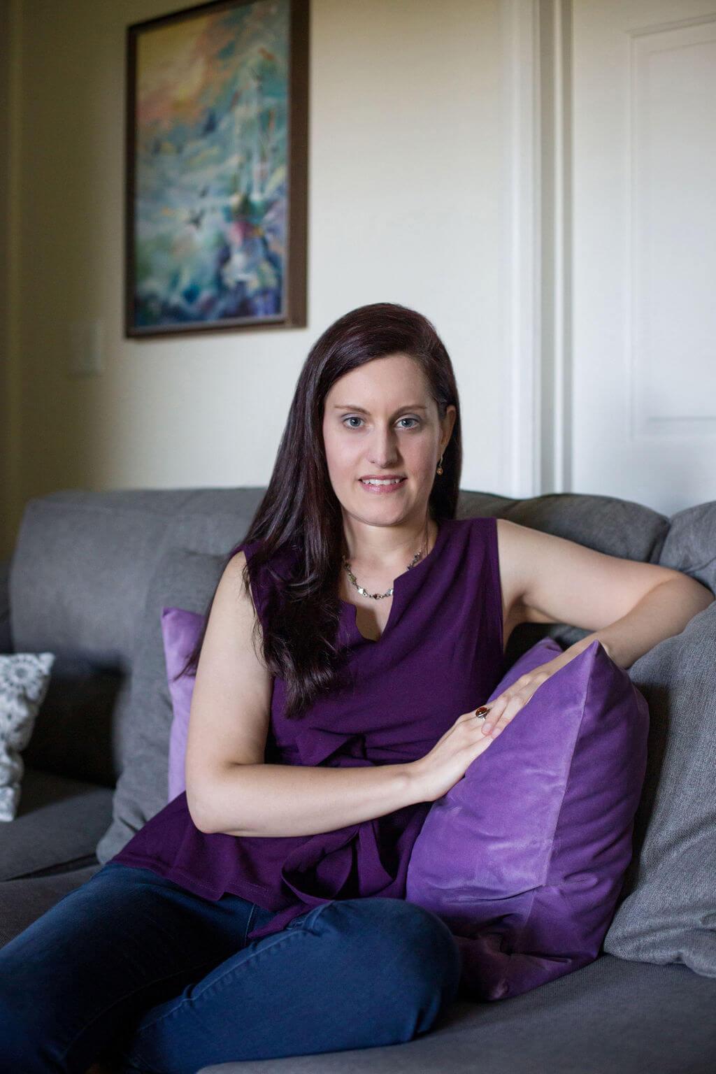 spiritual healer business coach on a grey sofa